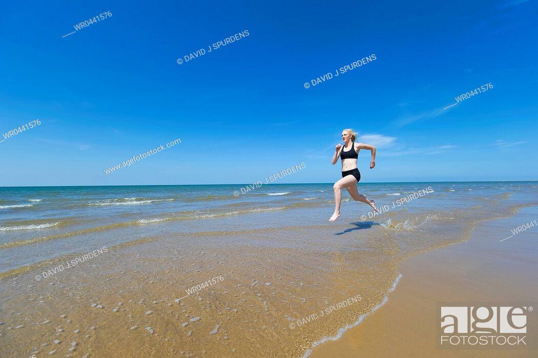 Stock Photo: Joggng along the oceans edge.