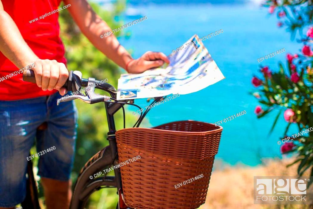 Stock Photo: Young traveling man with map of the island bicycling.