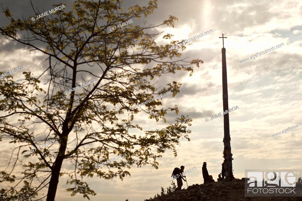 Stock Photo: Silhouette of pilgrims leaving stones at the base of Cruz de Ferro near the village of Foncebadon along the Camino de Santiago.