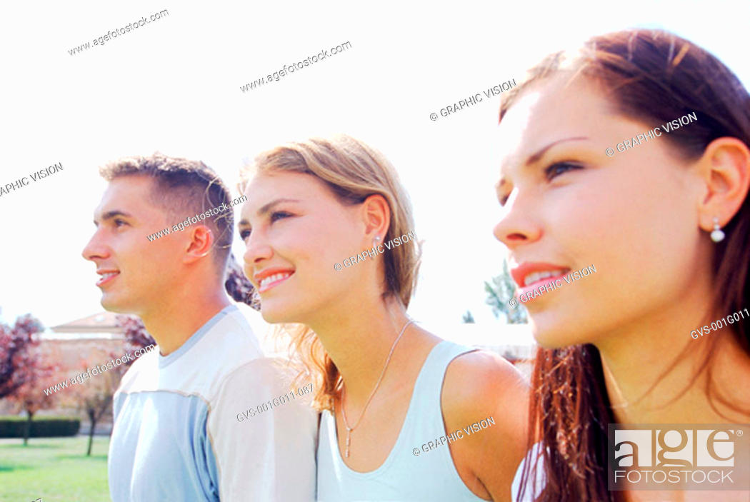 Stock Photo: Two young women standing with a young man.