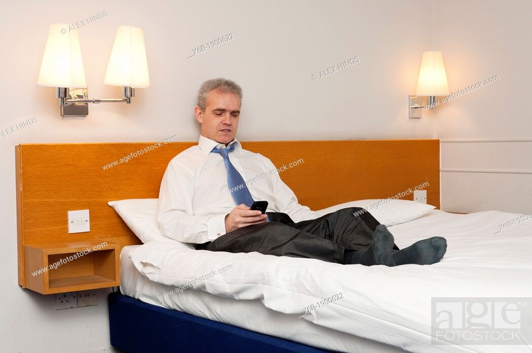 Stock Photo: Business man sitting on hotel bed checking his phone for messages.