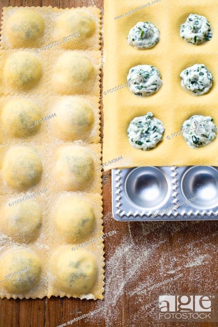 Stock Photo: Home-made soft cheese and herb ravioli in ravioli tray.