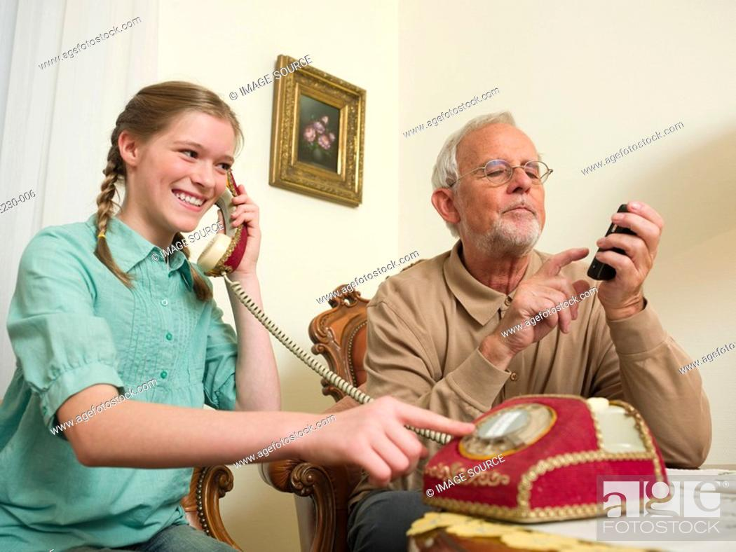 Stock Photo: Grandfather and granddaughter using telephones.