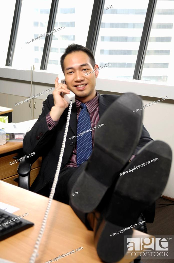 Stock Photo: Businessman talking on the telephone in an office.