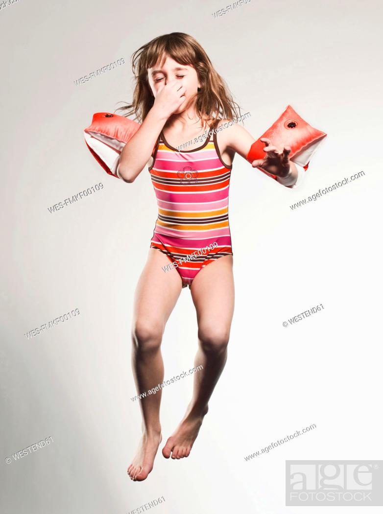 Stock Photo: Girl 7-8 wearing armband and jumping.