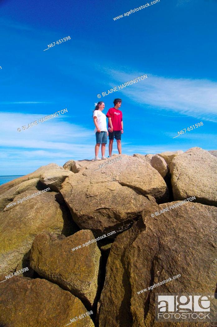 Stock Photo: 12 year old girl and her 15 year old brother standing on the rocks at Rock Harbor, Orleans, Cape Cod, Massachusetts, USA.