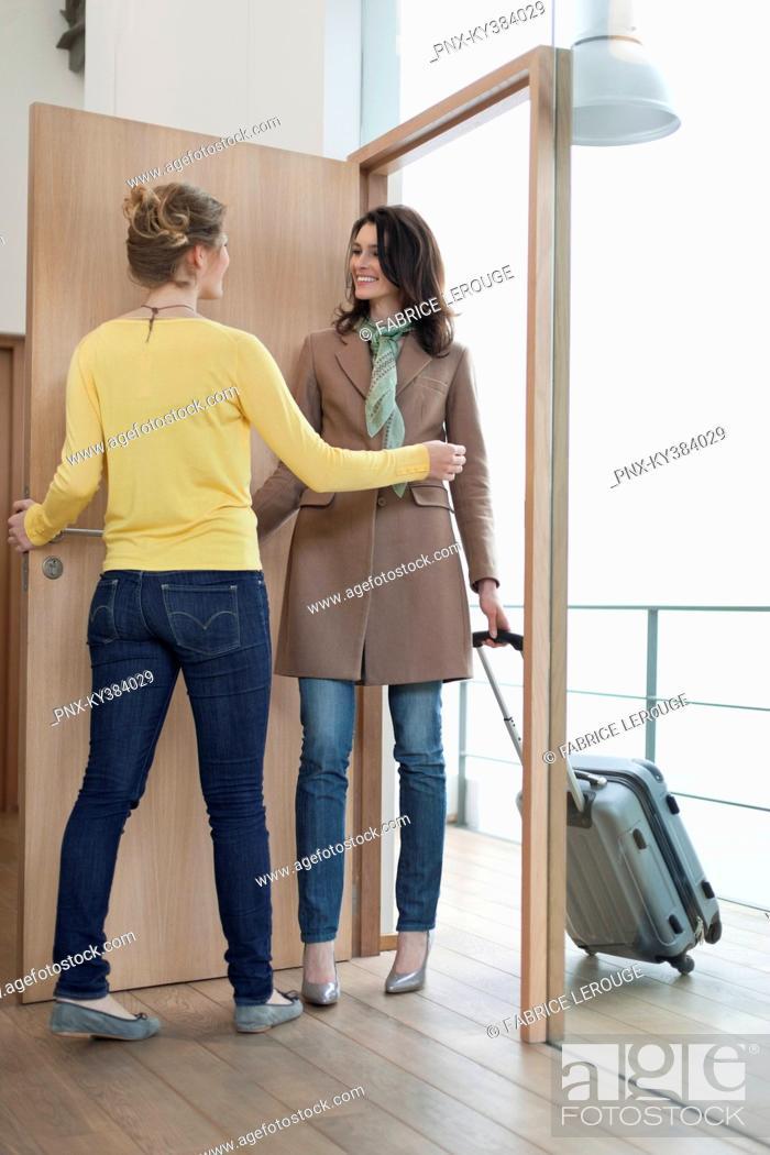 Stock Photo: Woman welcoming her friend at doorway.