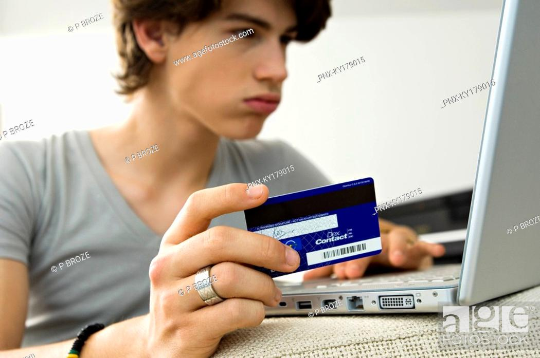 Stock Photo: Close-up of a teenage boy using a laptop and holding a credit card.