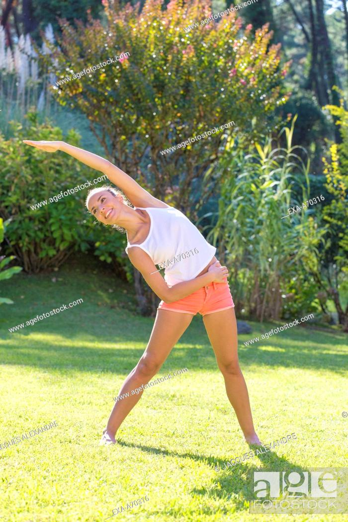 Imagen: Woman practicing exercise in park, summertime.