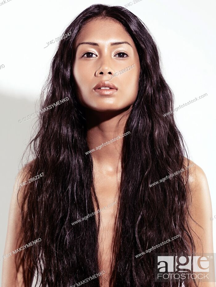 Stock Photo: Expressive artistic beauty portrait of a beautiful young exotic woman with very long wavy brown hair, front view on white background.