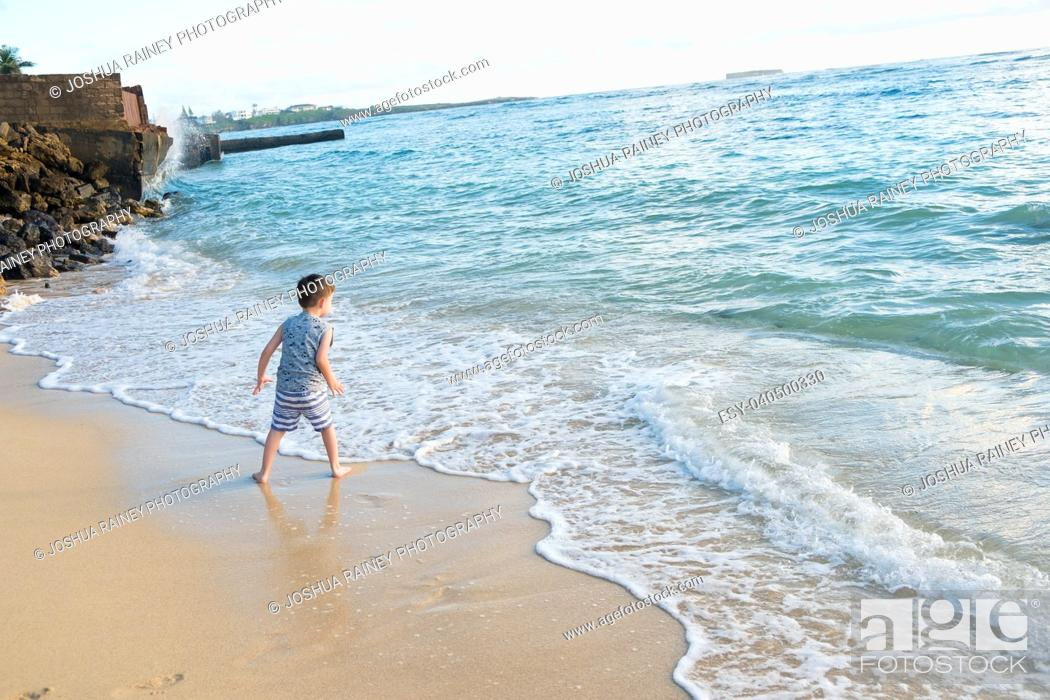 Stock Photo: Five year old boy playing in the waves of the Pacific Ocean and having fun while on vacation in Oahu Hawaii.