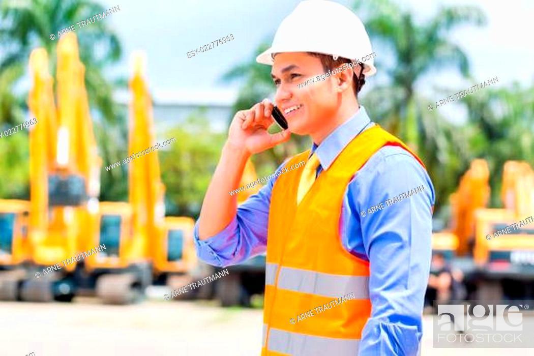 Stock Photo: Asian supervisor telephoning on construction site.