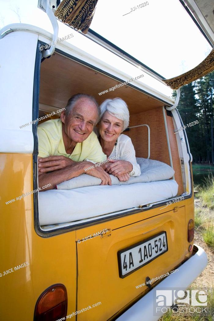 Stock Photo: Senior couple lying in back of camper van, smiling, portrait, low angle view.