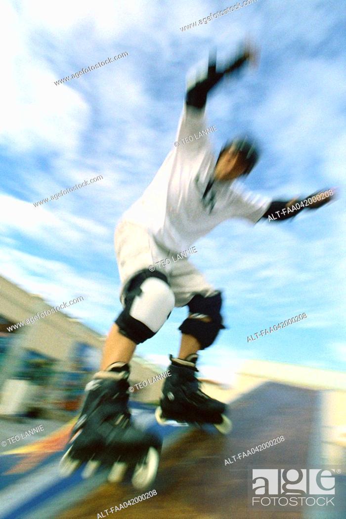 Stock Photo: Inline skater with arms raised sliding on ramp at skatepark.