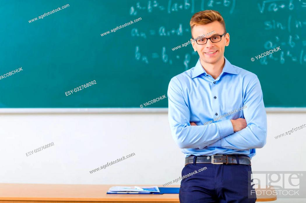 Stock Photo: College professor. Handsome young college professor smiles charmingly while folding his arms and leaning against the desk.