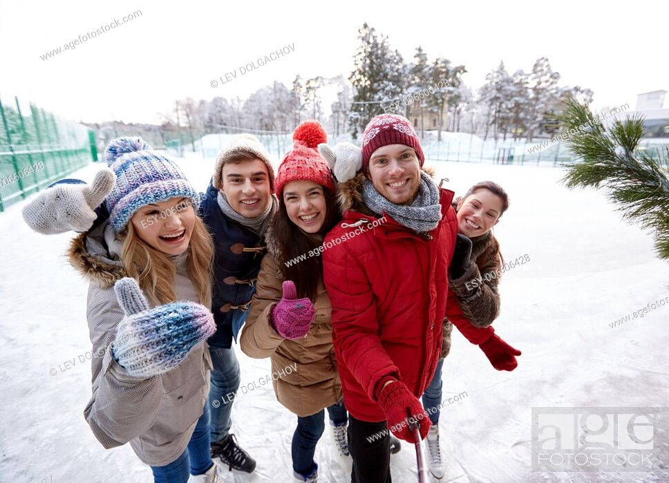 Stock Photo: people, friendship, technology and leisure concept - happy friends taking picture with smartphone selfie stick and showing thumbs up on ice skating rink.