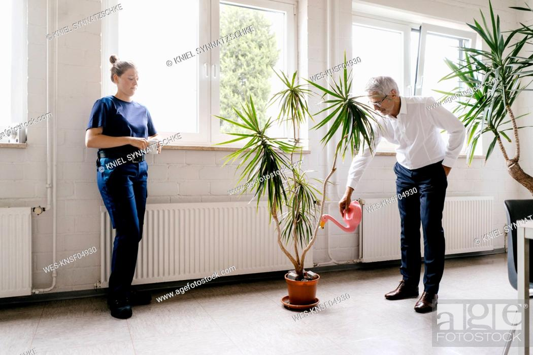 Stock Photo: Manager watering plants in recreation room, while worker is drinking coffee.