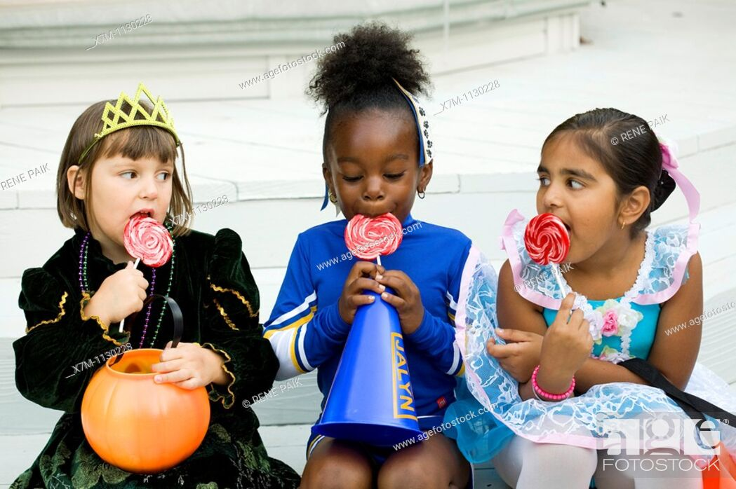Stock Photo: Little girls dressed in Halloween costumes enjoy their lollipops.