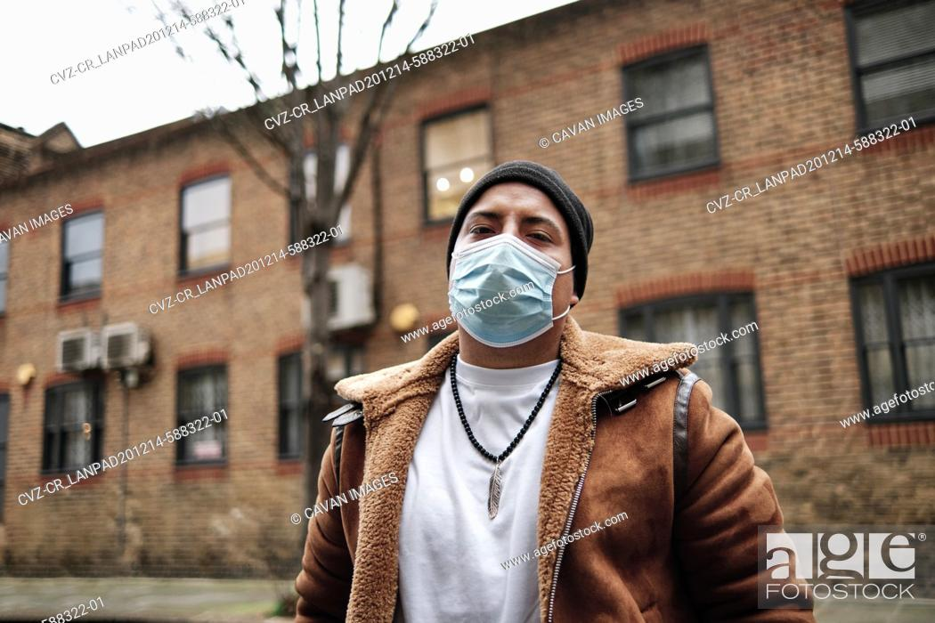 Stock Photo: middle aged latino man with a serious expression wearing a face mask outside looking at camera.