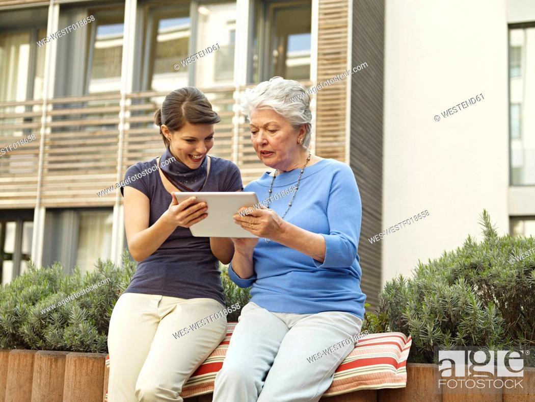 Stock Photo: Germany, Cologne, Women looking digital tablet outside of nursing home.