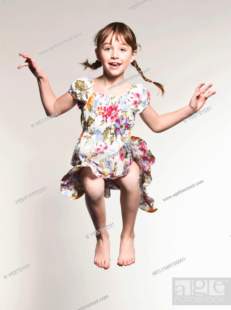 Stock Photo: Girl 6-7 jumping against gray background, portrait, smiling.
