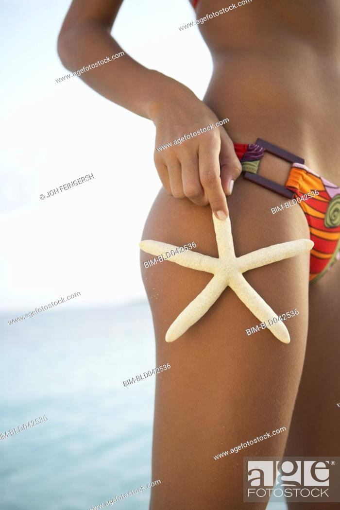 Stock Photo: South American woman holding starfish on thigh.
