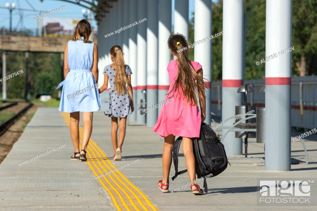 Stock Photo: A girl and a daughter walk along the platform of the railway station, another girl with a large backpack catches up with them.