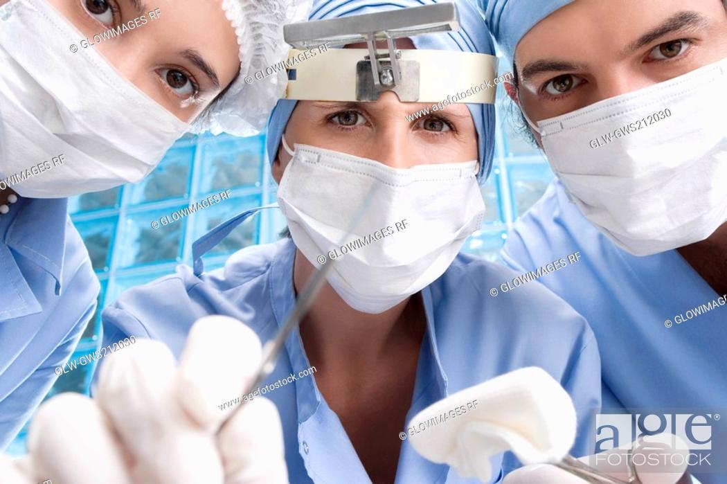 Stock Photo: Close-up of two female surgeons and a male surgeon in an operating room.
