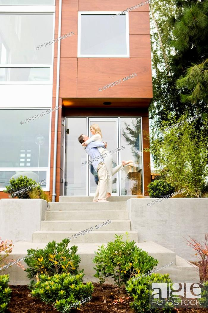 Stock Photo: Man hugging and lifting woman on front stoop of modern house.