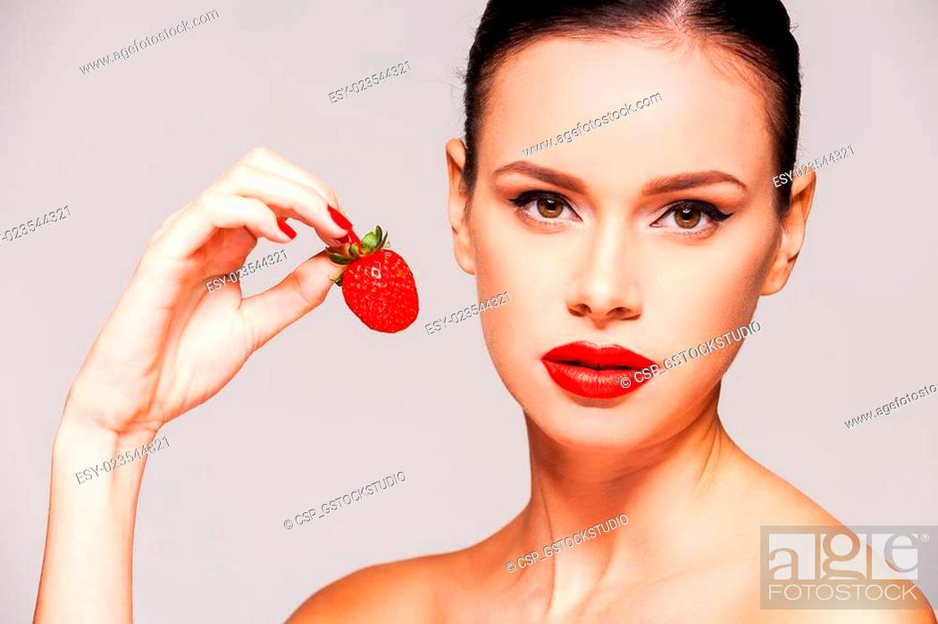 Stock Photo: Sweet temptation. Beautiful young shirtless woman holding strawberry in her hand while standing against grey background.