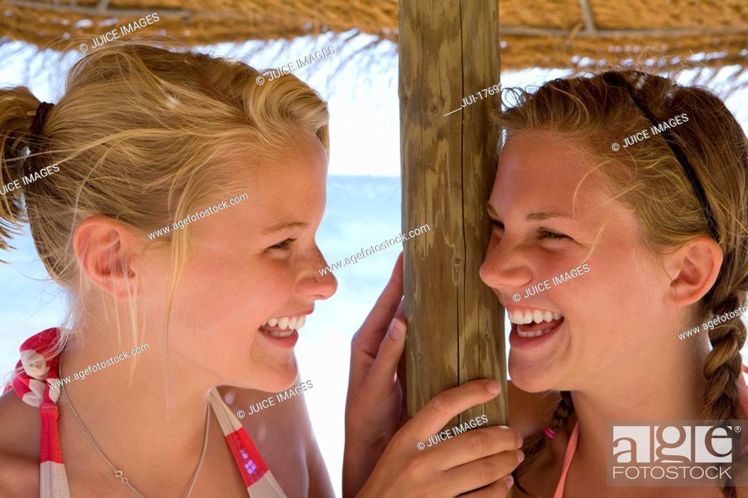Stock Photo: Teenage girls laughing under beach umbrella.