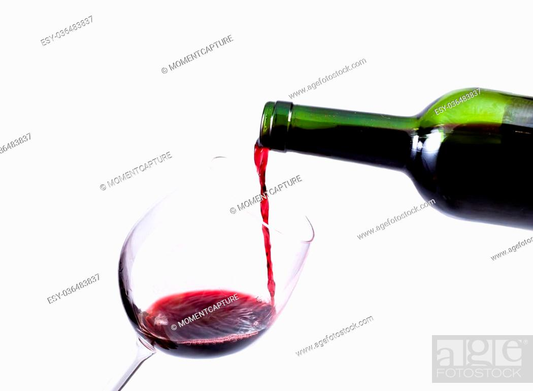 Stock Photo: red wine pouring in the glass isolated over white background.