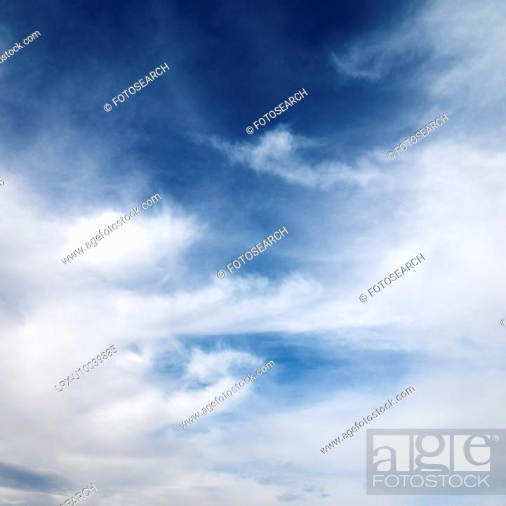 Stock Photo: Wispy cloud formations against clear blue sky.