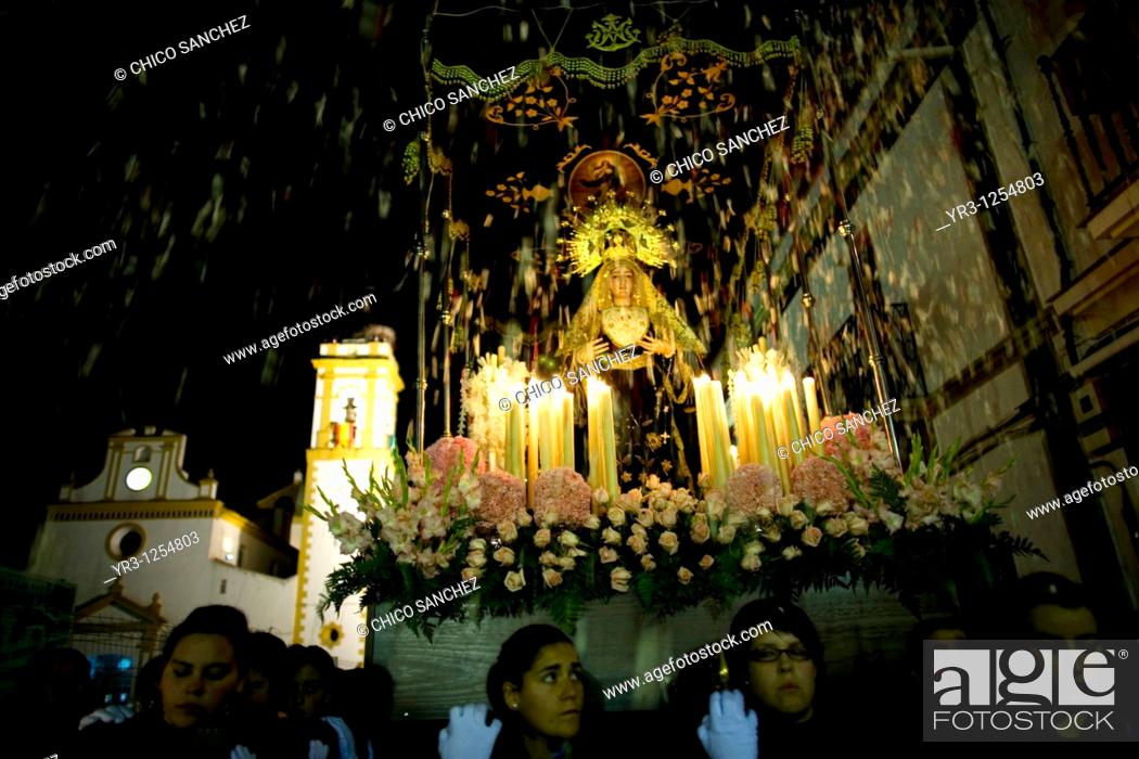 Stock Photo: People throw flowers toward a wooden statue of the Virgin of Pain as she is publicly displayed in a Holy Week procession in the town of Prado del Rey in.
