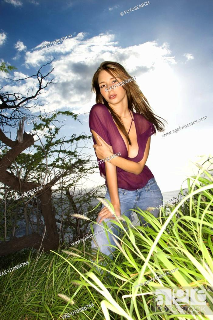 Stock Photo: Portrait of sexy young Caucasian woman standing on edge of grassy coastline looking at viewer.