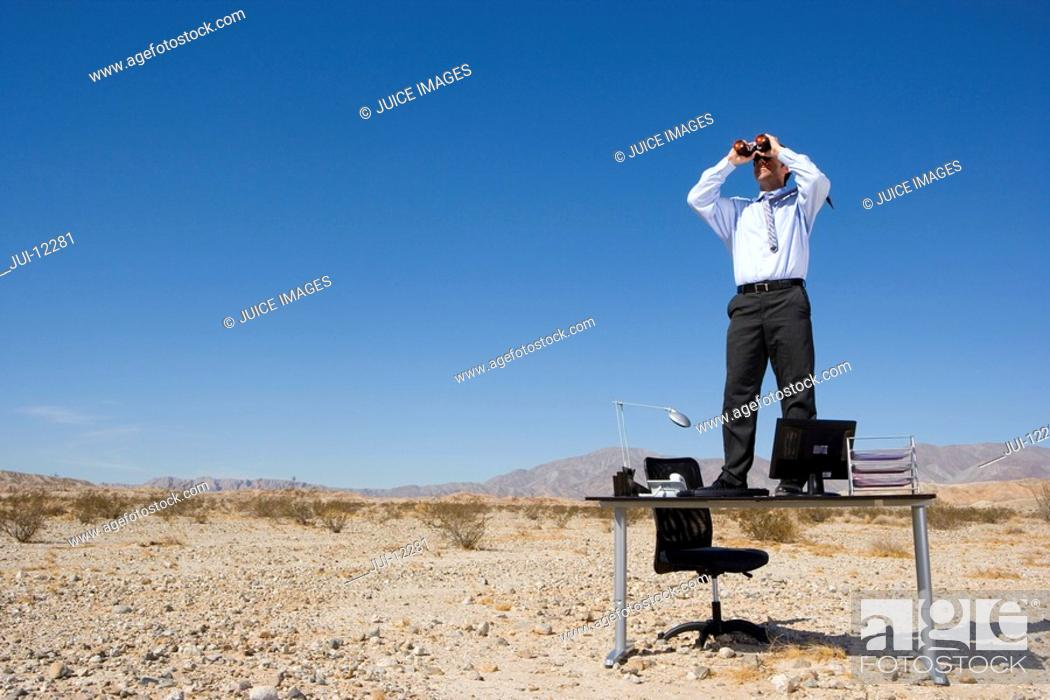 Stock Photo: Businessman standing on desk in desert, using binoculars, low angle view.