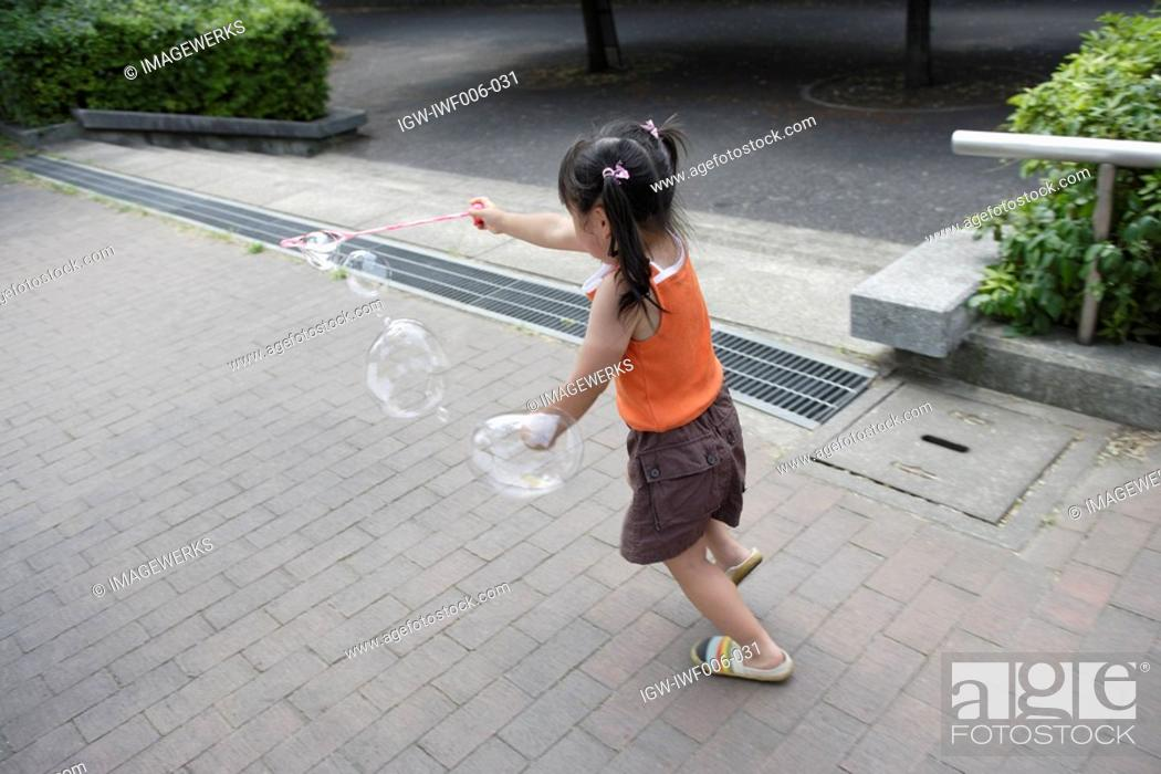 Stock Photo: A girl playing bubbles.