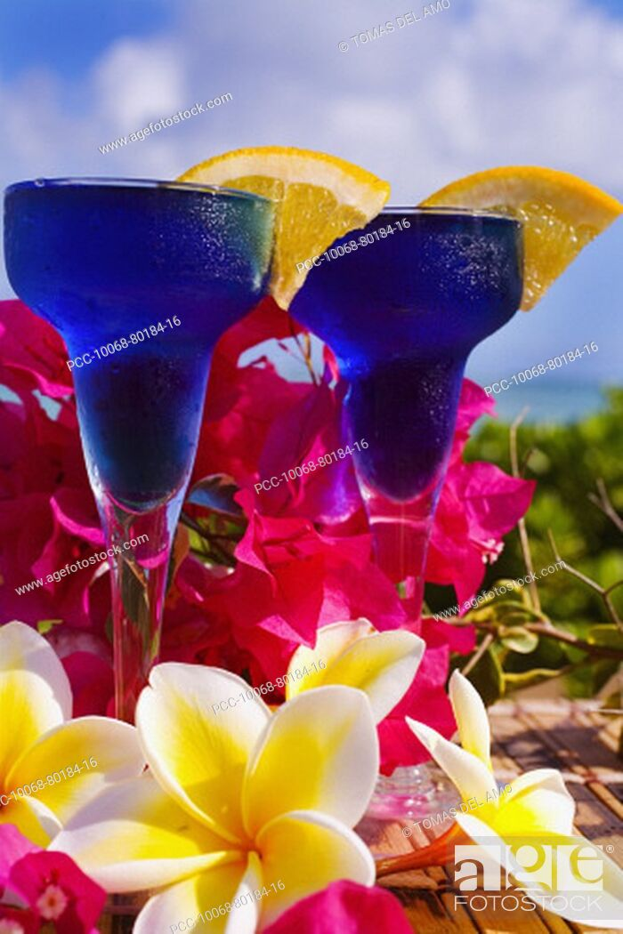 Stock Photo: Two tropical cocktails garnished with flowers in outdoor setting.