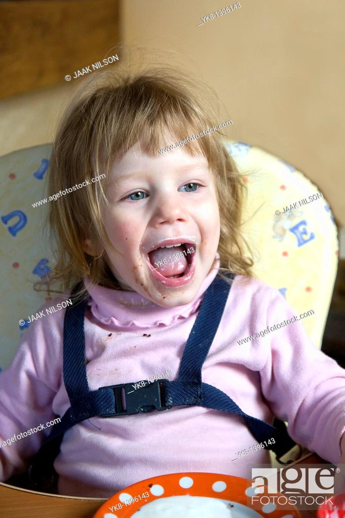 Stock Photo: Happy Dirty Two Year Old Caucasian Kid Girl Sitting and Shouting in High Chair.