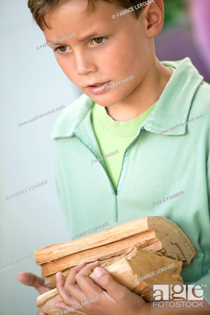 Stock Photo: Boy holding firewood.