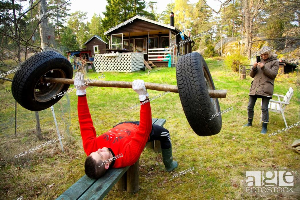 Stock Photo: Man benchpressing in nature with homemade barbell, swedish archipelago.