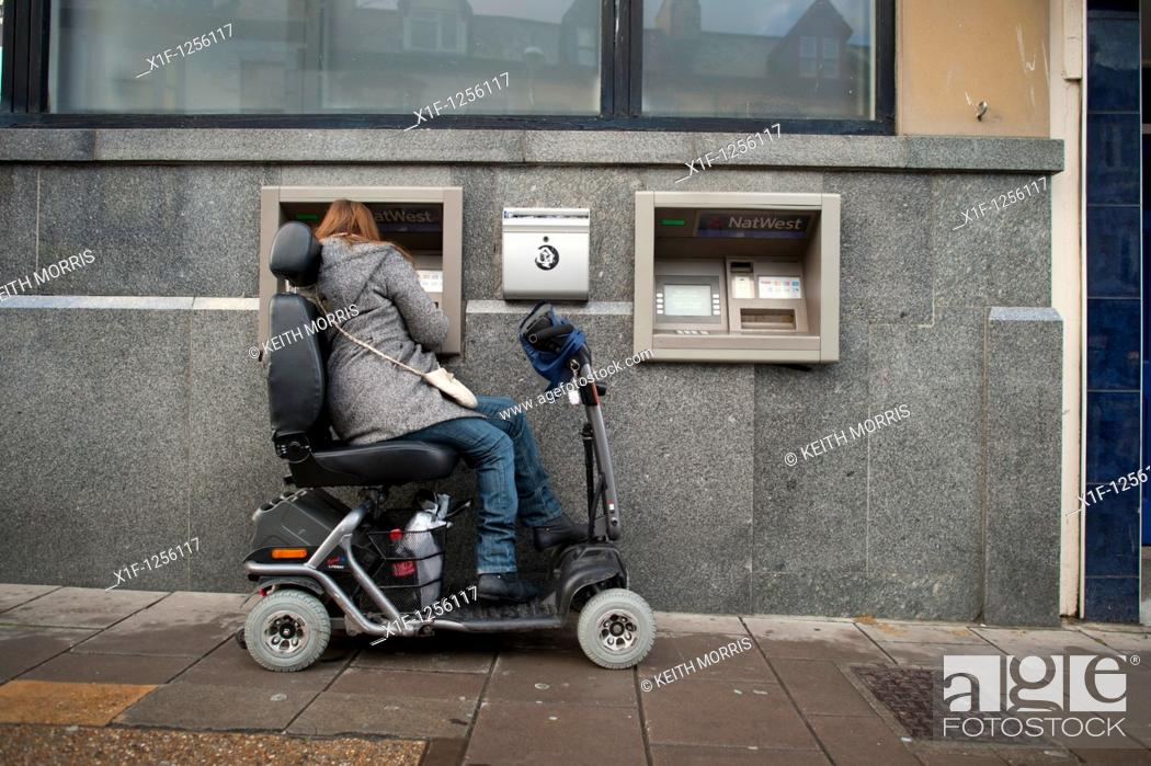 Stock Photo: a woman in a powered wheelchair scooter using an ATM cash machine, UK.