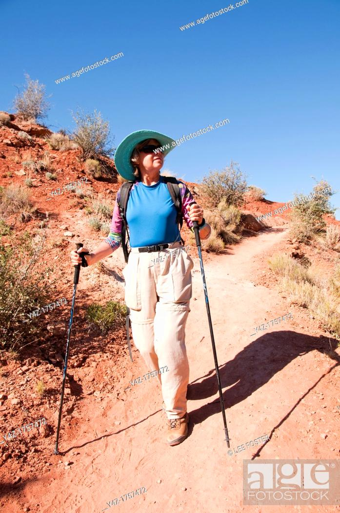 Stock Photo: USA, Utah, woman hiking at Escalante at Escalante Petrified Forest State Park to enjoy the petrified wood, views of the Grand Staircase and Colorado Plateau.