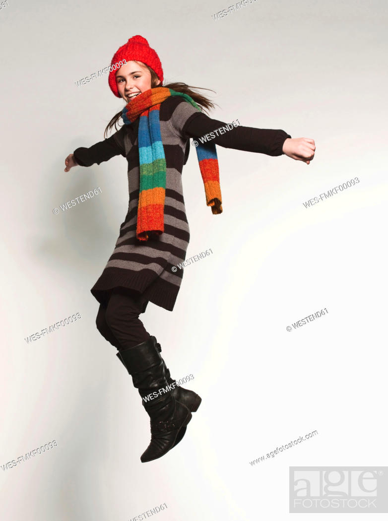 Stock Photo: Girl 10-11 jumping with arms stretched, portrait, smiling.