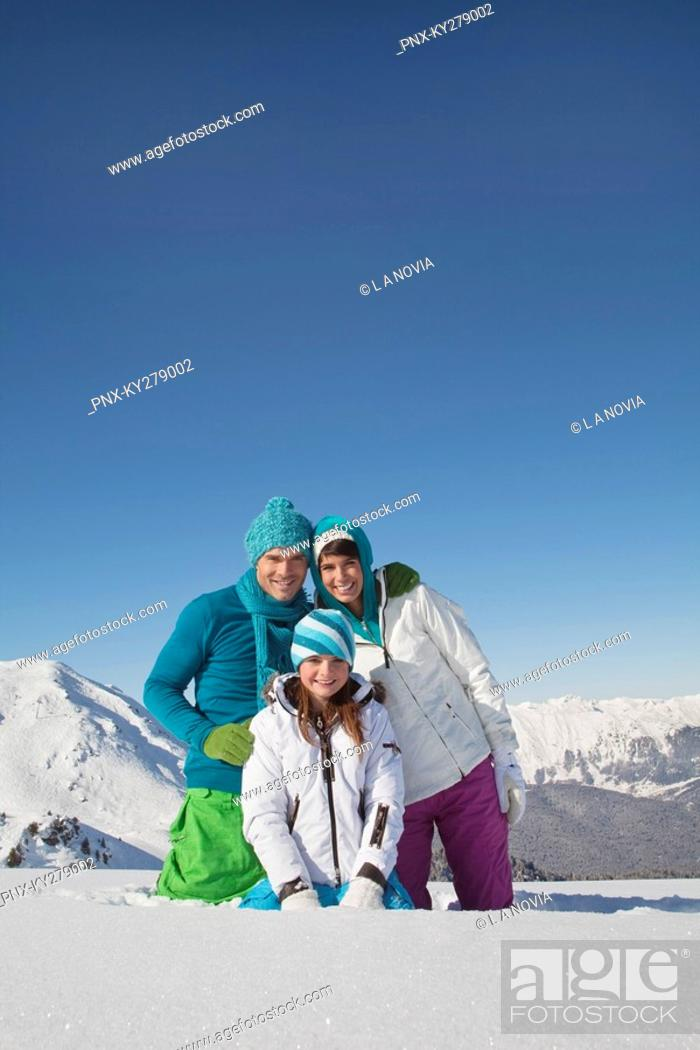 Stock Photo: Couple and daughter in ski wear, smiling at camera.