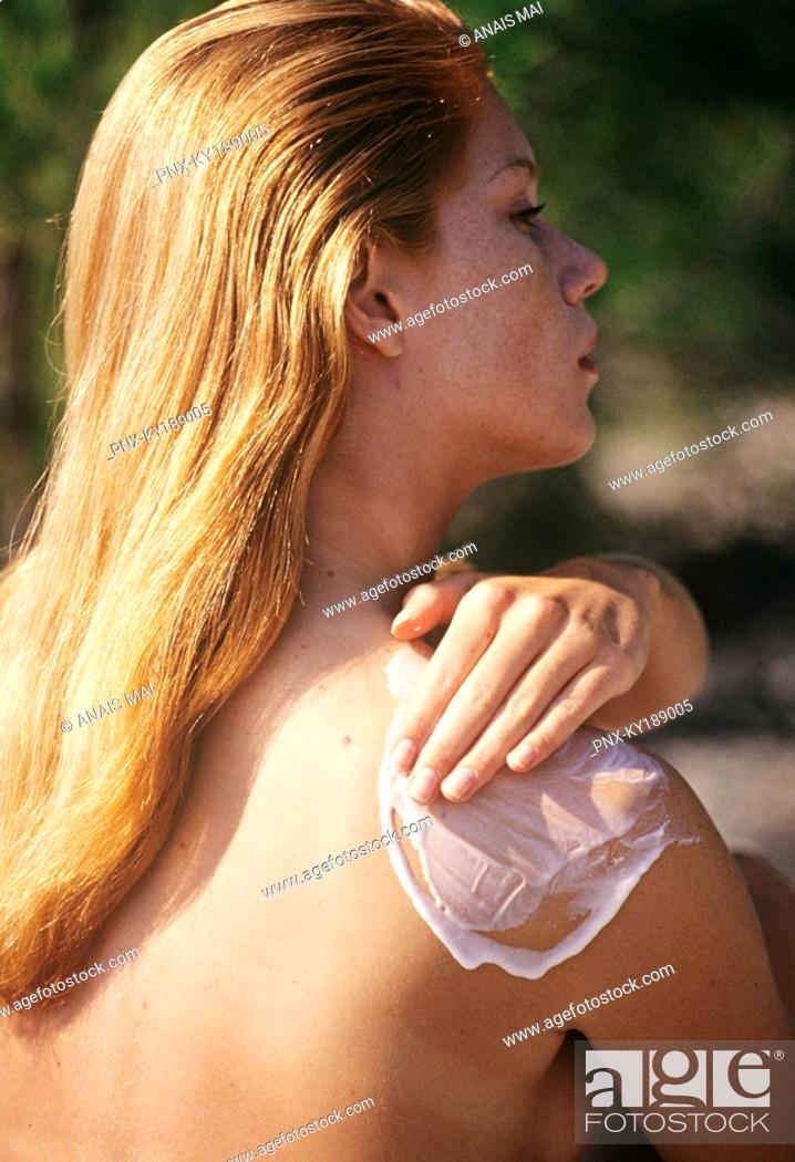 Stock Photo: Naked young woman applying suncream on her shoulder, outdoors.