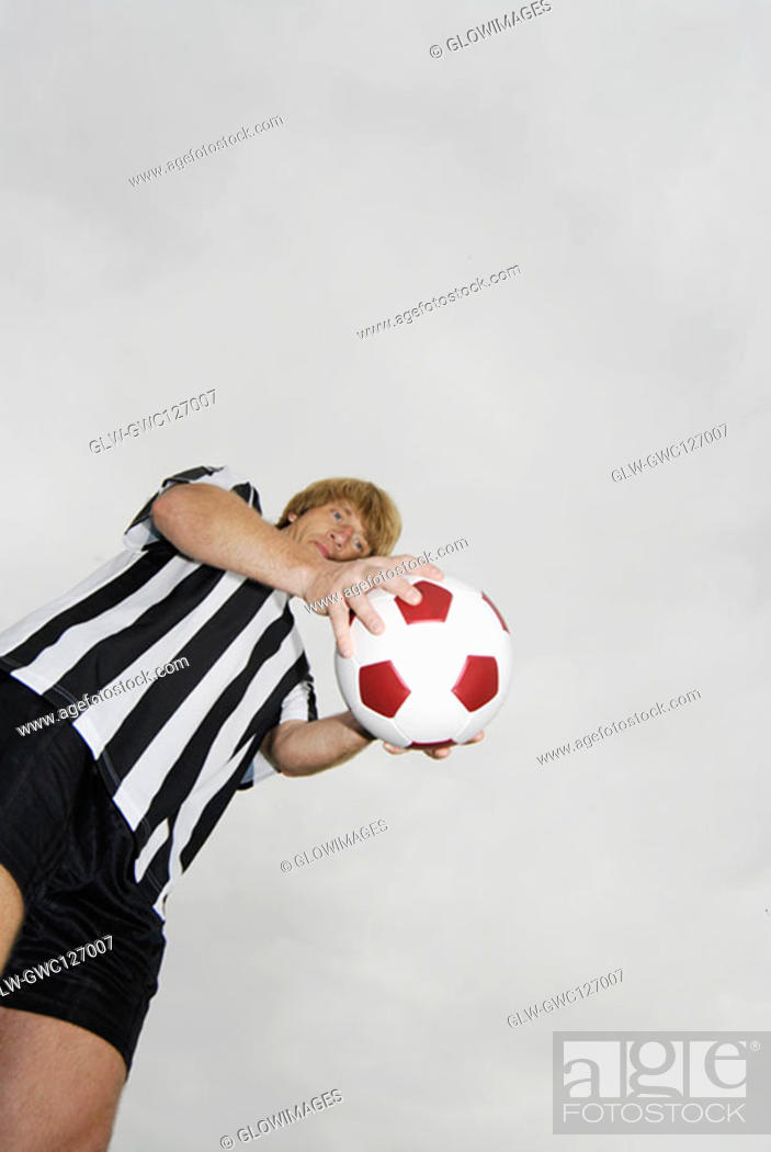 Stock Photo: Low angle view of a soccer player holding a soccer ball.