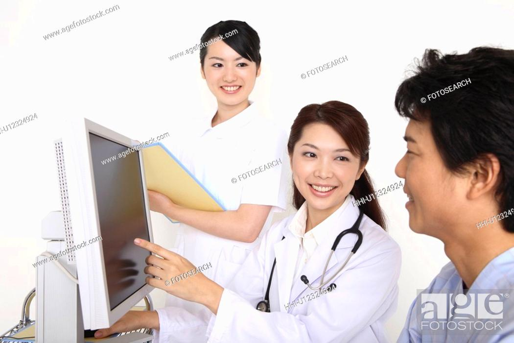 Stock Photo: Doctor explaining by a monitor.