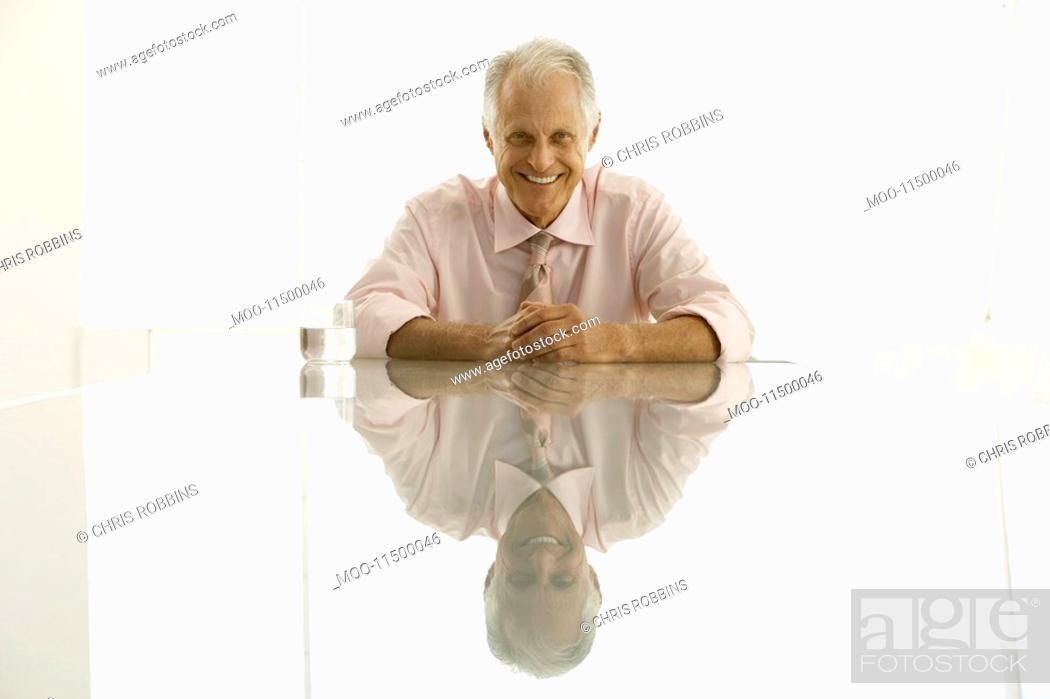 Stock Photo: Businessman sitting at table smiling portrait.