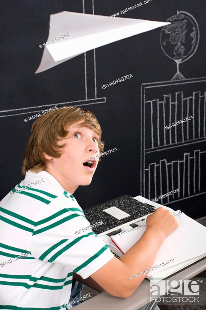 Stock Photo: A boy with a paper airplane over his head.